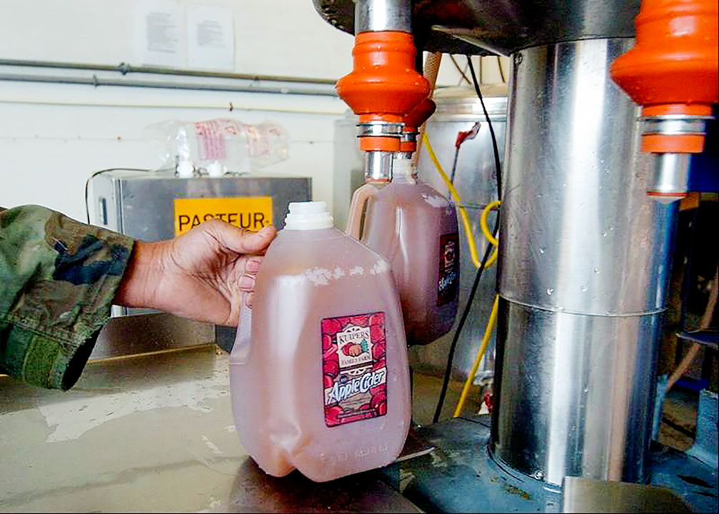 Apple cider filled into gallons after pasteurization at Kuipers Family Farm. [Photo: Bob Chwedyk/Daily Herald